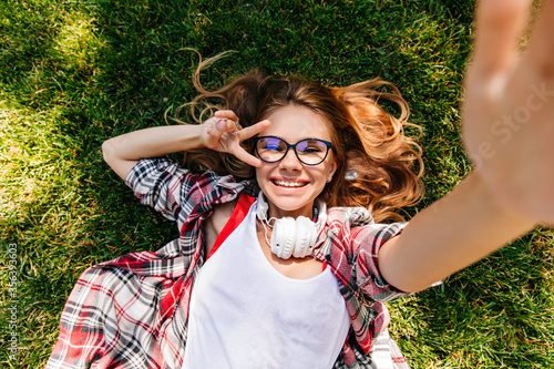 Fotografia Pleasant caucasian lady making selfie while lying on lawn