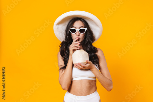 Carta da parati Image of pleased young woman in swimsuit and hat drinking coconut water
