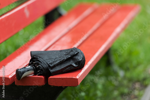 Forgotten black folded wet rain umbrella lying on wooden park bench during heavy Canvas Print