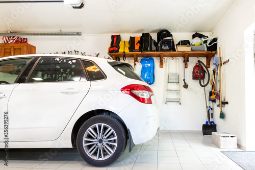 Photo Home suburban car garage interior with wooden shelf , tools and equipment stuff storage warehouse on white wall indoors