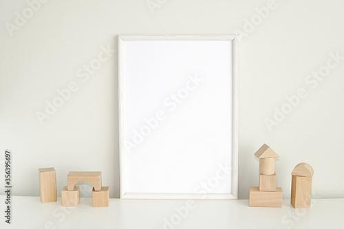 Fototapeta White frame mockup for nursery or kids room, blank photo frame and wooden cubes. obraz