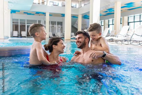 Fototapeta Smiling family of four having fun and relaxing in indoor swimming pool at hotel resort. obraz na płótnie