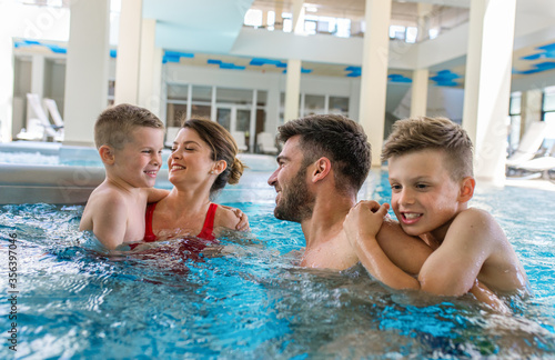 Photo Smiling family of four having fun and relaxing in indoor swimming pool at hotel resort