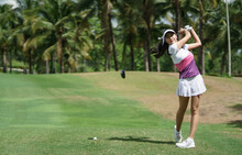 Asian Female Golfer Swinging Club On Golf Course Green With Copy Space.