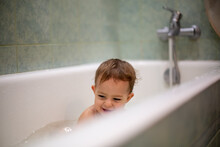 Cute Caucasian Baby Take A Bath, Playi In Bath And Smiles Looking At  Water Splashes, In The Background A Green Bathroom In Blur. Close-up, Soft Focus