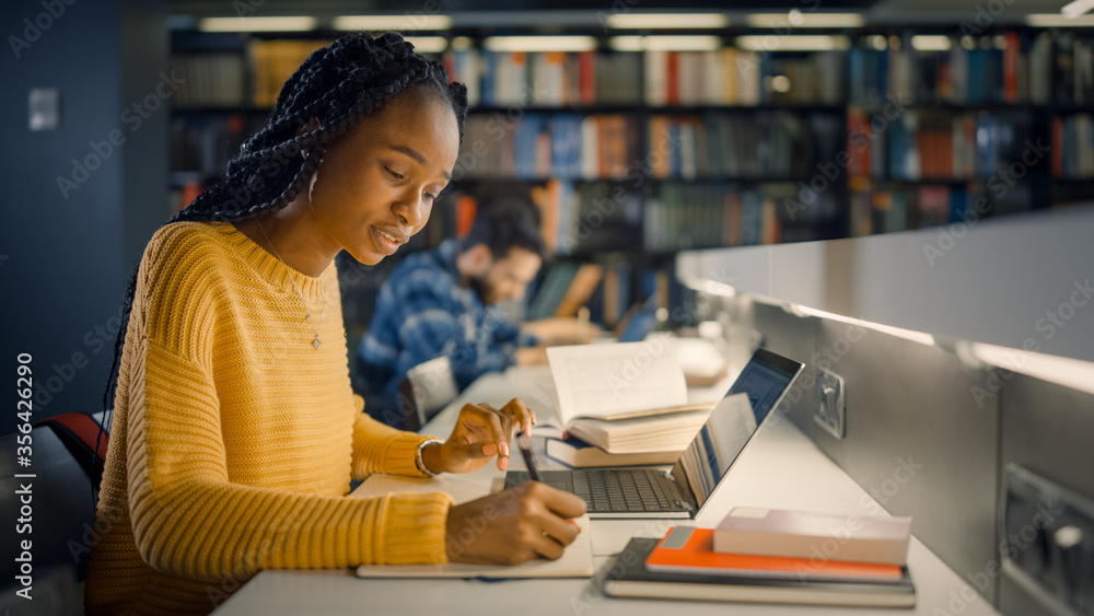 Fototapeta University Library: Gifted Beautiful Black Girl Sitting at the Desk, Uses Laptop, Writes Notes for the Paper, Essay, Study for Class Assignment. Diverse Group of Students Learning, Studying for Exams.