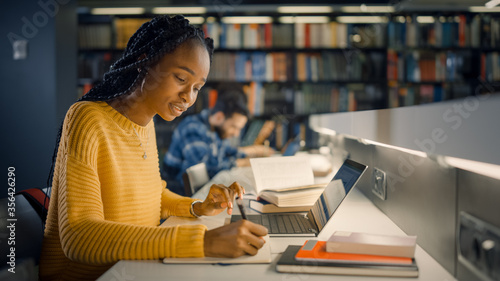 Tablou Canvas University Library: Gifted Beautiful Black Girl Sitting at the Desk, Uses Laptop, Writes Notes for the Paper, Essay, Study for Class Assignment