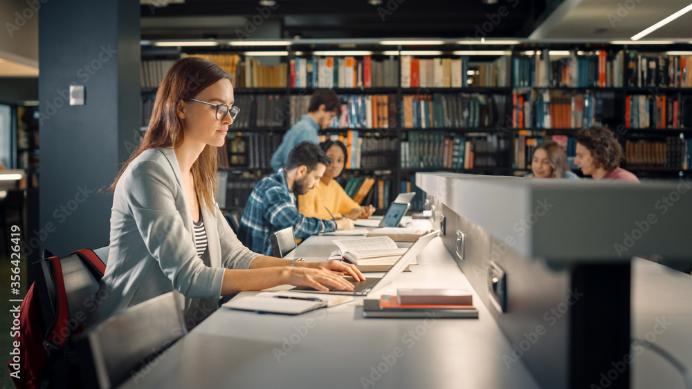 Fototapeta University Library: Talented Caucasian Girl Sitting at the Desk, Uses Laptop, Writes Notes for the Paper, Essay, Study for Class Assignment. Diverse Group of Students Learning, Studying for Exams.