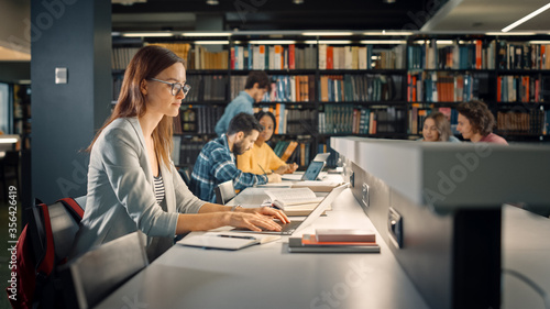Fotomural University Library: Talented Caucasian Girl Sitting at the Desk, Uses Laptop, Writes Notes for the Paper, Essay, Study for Class Assignment