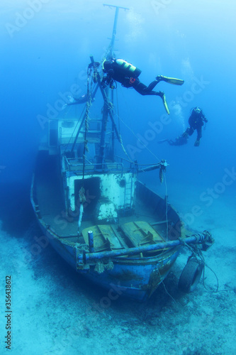 Scuba Divers Exploring underwater ship wreck Fototapeta