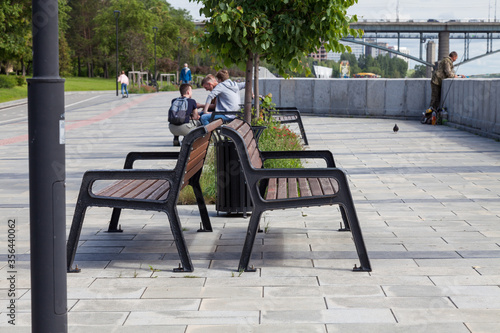 Obraz City park with a promenade covered with paving slabs and wooden benches where people relax and against the background of a car bridge and a fisherman and a child riding on skateboard on bicycle path. - fototapety do salonu