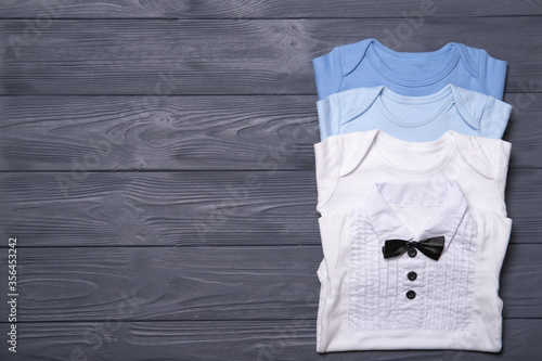 Fototapeta Baby clothes on a gray background. Place for text. Flat lay