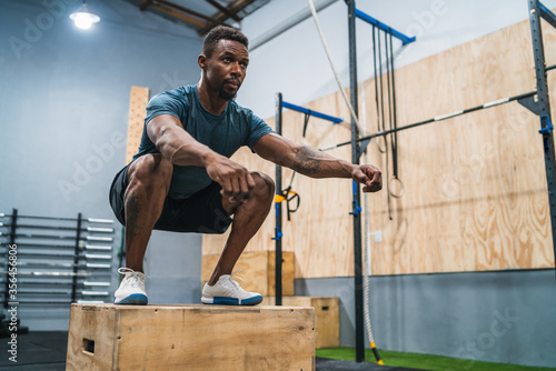 Athletic man doing box jump exercise. Wallpaper Mural