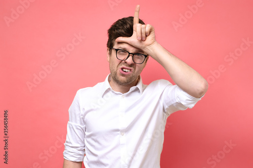 Young caucasian boy in glasses showing looser sign Принти на полотні
