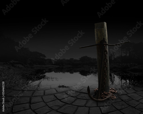 Photo The anchor aslant stand beside of stump at the edge of a river