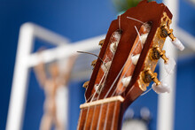 Wooden Guitar Head With Ring Gears On Blue Blurred Background