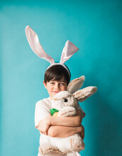 Boy Wearing Bunny Ears Hugging Toy Rabbit Against Blue Background.