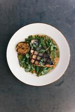 Grilled Salmon Filet Over Green Harvest Vegetables And Lemon On Table