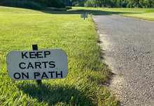 Golf Course Signs Display That Golf Carts Are To Remain On The Cart Path
