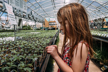 Close Up Of Girl Looking At Plants In Greenhouse