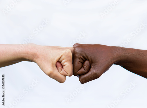 Fototapeta Two hands of different racial colors, punching each other, expressing victory, agreement, partnership. The concept of ending racism obraz