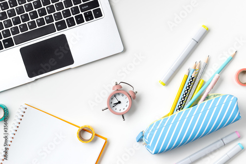 Fotomural Flat lay top view laptop, pencil case and stationery on white table
