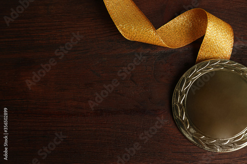 Fotografía Gold medal with ribbon on wooden background, flat lay