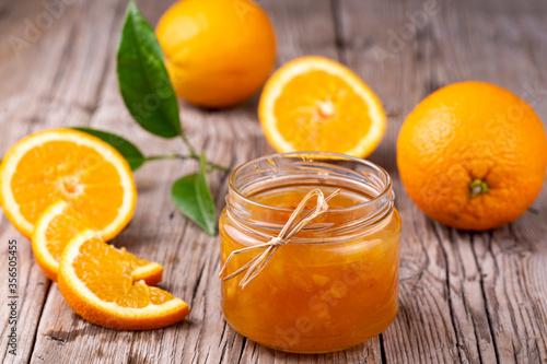 Fototapeta Orange jam in glass jar on wooden background. obraz