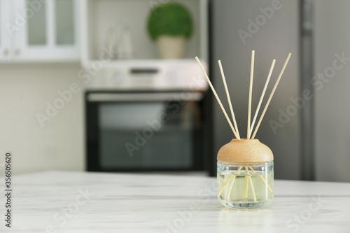 Fotografie, Obraz Aromatic reed air freshener on white marble table indoors