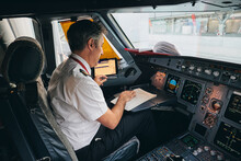 Side View Of Male Captain Sitting In Cockpit Of Contemporary Aircraft And Reading Flight Document While Preparing For Departure