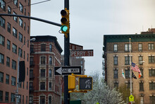 Low Angle Of Signpost With Various Road Signs And Green Traffic Light In Old District Of New York City With Weathered Buildings On Background