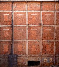 Shabby Old High Wall Of Abandoned Red Brick Building With Brick Windows Ruined Entrance And Pipes With Dirty Black Smudges