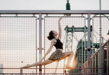 Low Angle Side View Of Serene Female Wearing Summer Outfit Doing Yoga In Crescent Lunge Pose While Balancing On Metal Railing And Looking Up