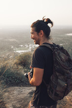 Side View Of Young Cheerful Male Traveler In Casual Clothes With Haversack Standing On Edge Of Cliff And Taking Picture Of Majestic Landscape Of Green Forest During Sunset