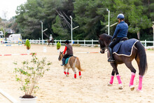 Back View Of Boy On Roan Pony And Teen Girl On Brown Horse Riding Horses On Dressage Arena During Lesson In Equestrian School