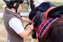 Side View Of Little Jockey In Protective Helmet Adjusting Stirrup On Saddle Before Riding Skewbald Pony In Equestrian School