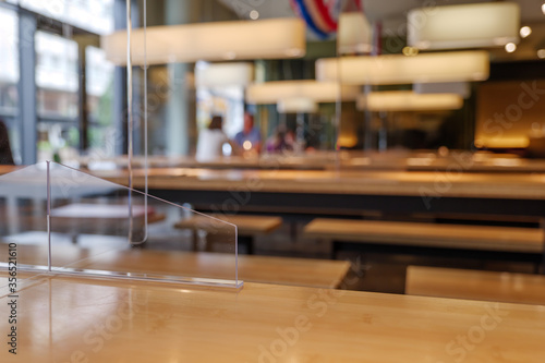 Photo Selected focus view at temporary transparent acrylic partition on wooden table to make Social Distancing in reopening Restaurant during epidemic of COVID-19 with New Normal concept