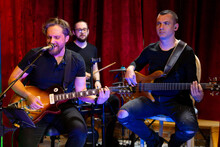 The Band Of Musicians Playing Electric Guitar, Bass Guitar And Drums During The Concert Broadcast Online On Social Media Platforms In The Bar.