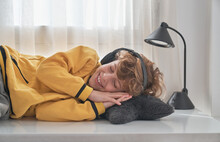 Happy Preteen Boy In Headphones And Casual Clothes Lying With Eyes Closed On White Table And Listening To Music With Pleasure While Lounging At Home