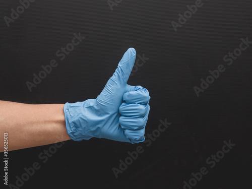 Photo Mano afirmando con guante de latex celeste, proteccion con bioseguridad