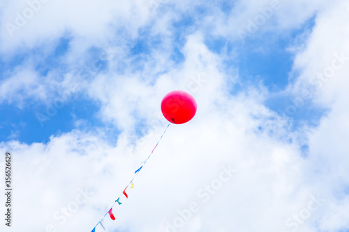Red helium balloon high in the blue sky with clouds