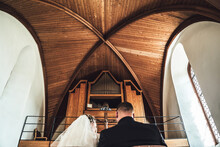 Rear View Of Marriage Couple In Front Of Altar In Church. Focused On Woman Playing At Pipe Organs. Wood-paneled Vaulted Ceiling.