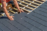 Fototapeta Dmuchawce - Craftsmen are installing a slate roof home.Professional roof workers repairing roof t.Working on rooftop.