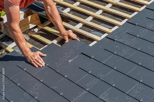 Fotografia Craftsmen are installing a slate roof home