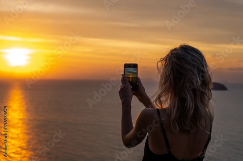 Woman hands holding mobile phone at sunset Canvas Print
