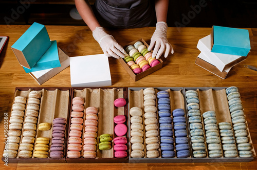 Female hands puts colorful macaroons in a paper box
