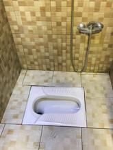 Asian Squat Toilet Shown In Tiled Restroom