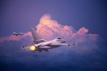 F-16 Fighting Falcon Jets (models) Fly Toward Pink And Purple Clouds At Sundown