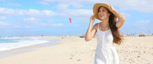 Panoramic Banner View Of Happy Young Woman Holding Her Straw Hat Walking On Desert Beach In A Windy Day