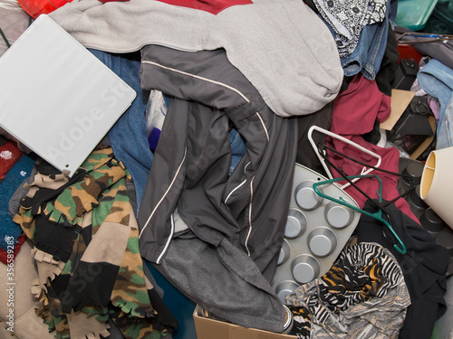 Fotografija Close-up color photo of messy pile of household items including hangers, muffin tins, binder, jacket, blanket and clothes almost completely covering couch